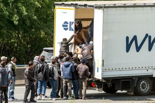 7779098413_des-migrants-embarquent-dans-un-camion-en-transit-dans-le-port-de-calais